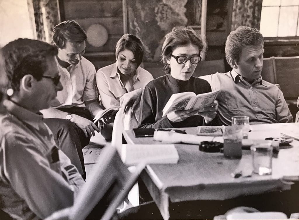Anne Bancroft and other actors sitting around a table with scripts beginning the reading of a play.