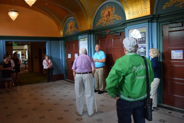 A tour group in the Historic Lobby of the Colonial Theatre stand under the golden ceiling and listen to Bill Munn conduct a tour.