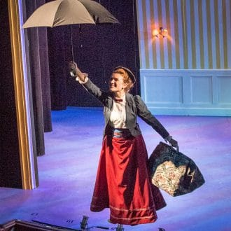 Mary Poppins flies over the audience with her umbrella raised.