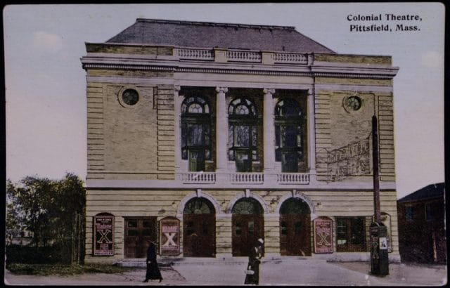 Postcard showcasing the front of The Colonial Theatre with people walking past in period garb.