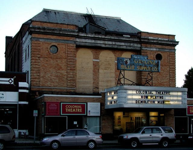 Exterior of The Colonial Theatre before Restoration. The Marquee is intact and lists, Colonial Theatre, Now Playing, Demolition Man. The Windows are boarded up, and the roof is in terrible shape.