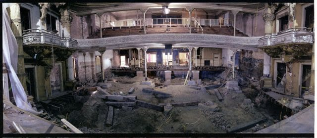 Looking out into the theatre from the stage during restoration. Debris line the floor, seats are ripped out, and various construction equipment is around.