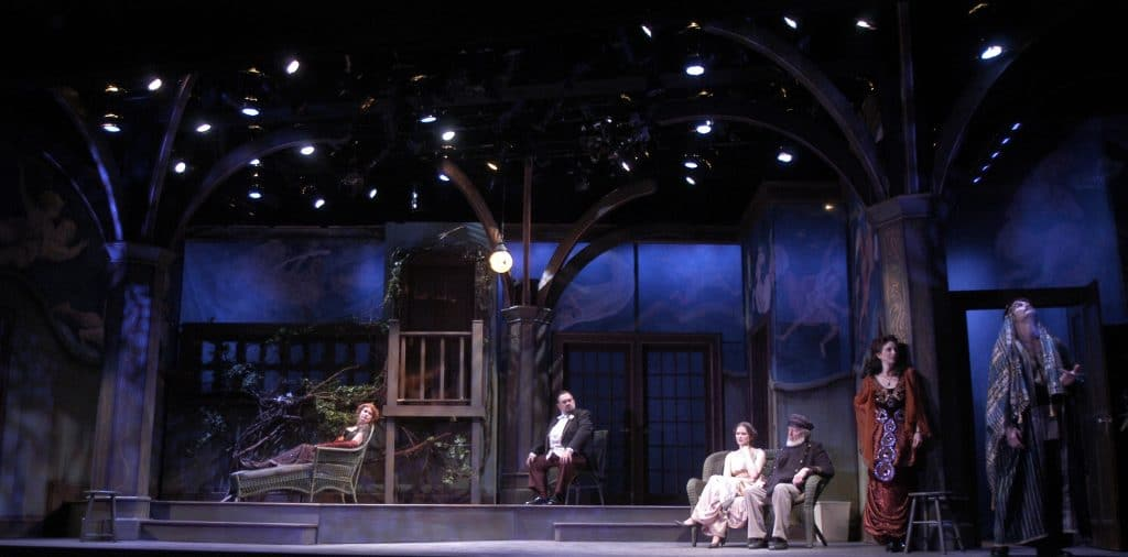 The photo depicts a scene from Heartbreak House, the stage is lit as if it is night, with the lighting instruments showing and arranged looking like trees. One woman is lounging on a sofa, three more sit in various chairs and loveseats, one woman is leaning against the column, which is part of the set, and another man stands and looks up and out.