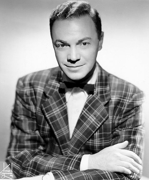 Headshot of Alan Freed. His arms are crossed and he is leaning toward the camera. He has a slight smile on his face and is wearing a plaid suit jacket, white undershirt, and bowtie.