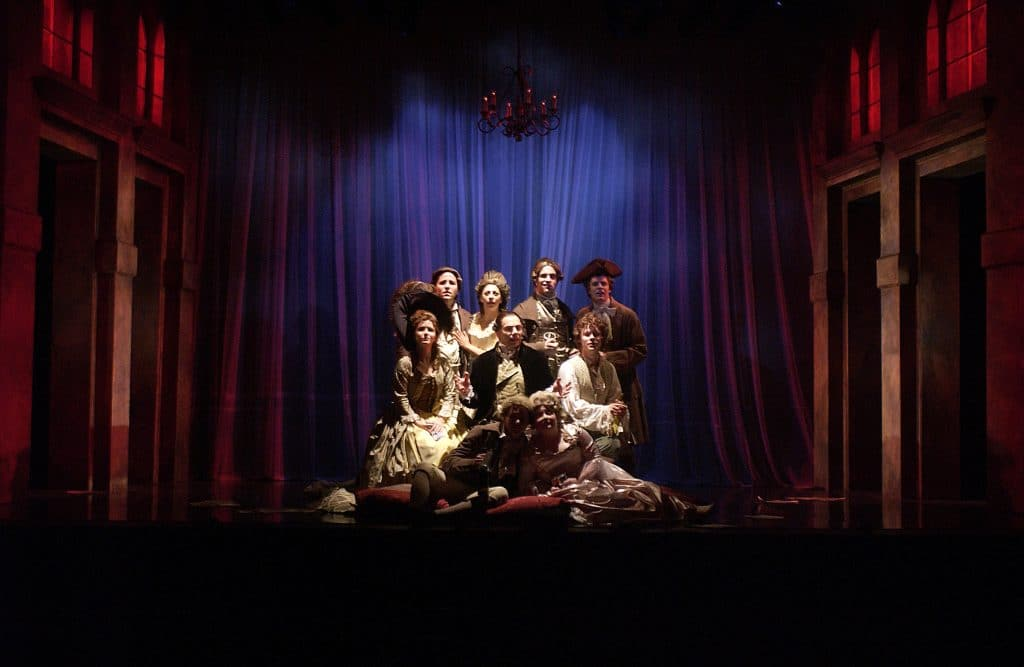 Photo depicts a scene from Amadeus with the cast center stage, intense red lighting on the set to the sides, and a deep blue onto the center create a unique lighting dynamic.