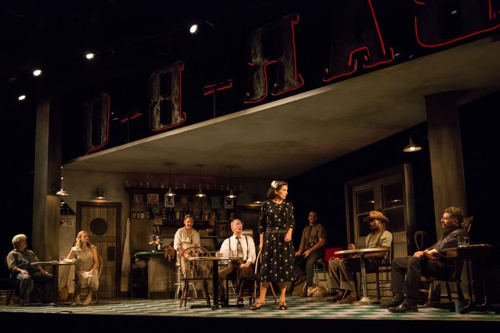 Photo depicts a scene from The Petrified Forest with nearly the full cast on stage, all are sitting or leaning, except for one woman. The columns are visible, and you can see the roof and neon sign.