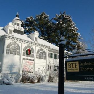 The Fitzpatrick Main Stage covered in snow. The angle is from the front, with the BTF sign visible. A wreath is hanging on one of the distinctive arches.