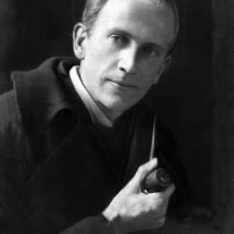 Picture of A. A. Milne partially turned to the camera holding a pipe with a wry smirk.