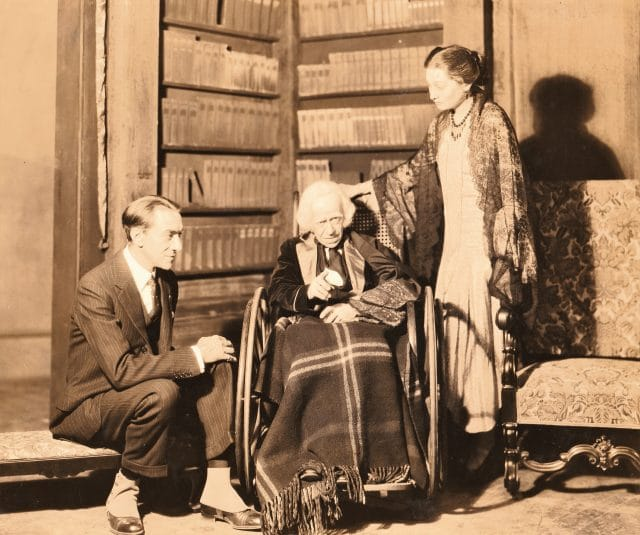 Donald Meek is sitting in a wheelchair with a plaid blanket on his lap. He is in front of a corner bookcase. Aline McMahon is on his left, standing, and Pedro de Cordoba is on his right, sitting on a step.