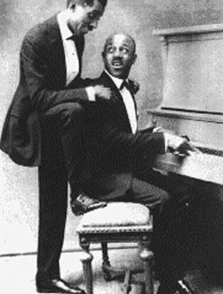 Eubie Blake and Noble Sissle are both in tuxes. Noble sits at the piano, playing, and looking back at Eubie who is standing behind him with hand on Noble's shoulders.