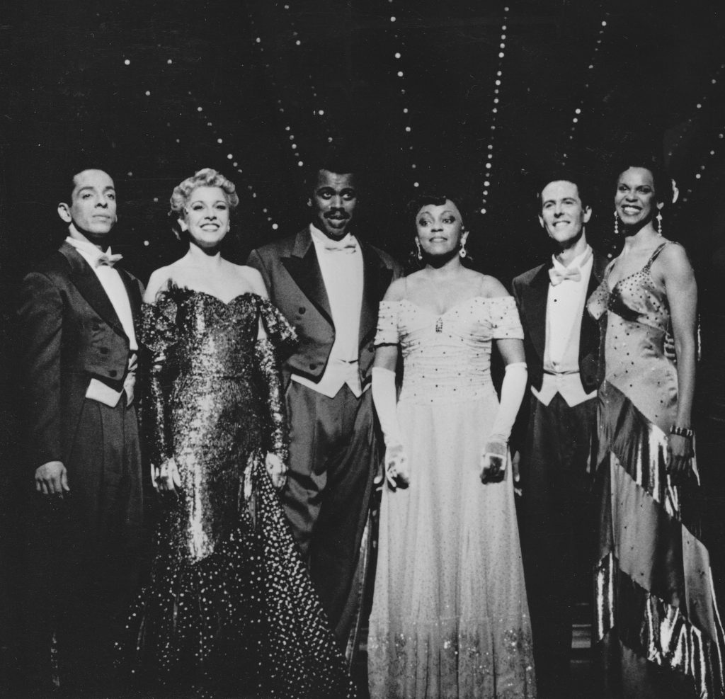 All of the actors are wearing formal wear and standing in a line on the stage.