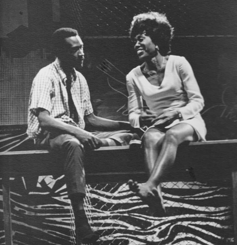 Barbara Ann Teer (right side) and Cleavon Little (left side) sit on a fence talking. Barbara's character is barefoot and there is a wall behind them decorated in tiger print.