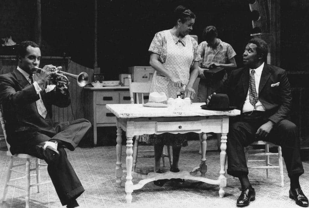 Three of the actors are around the kitchen table with Carrie Hamilton off in the background. David L. King is playing a trumpet, Frances is dealing with food, and John is leaning on the table.