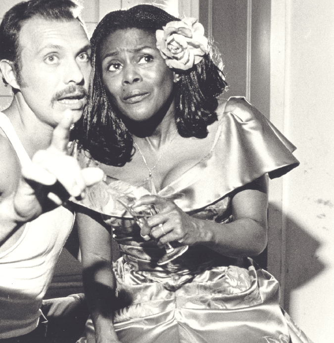 Cicely Tyson is wearing a garish dress and has a flower in her hair. She is clutching a drink in her hand and looking at something that Hector Elizondo is pointing to.