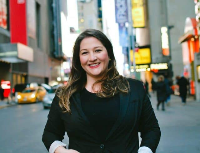 Ilana Ransom Toeplitz standing in a NYC street. She is smiling and wearing a dark blazer.