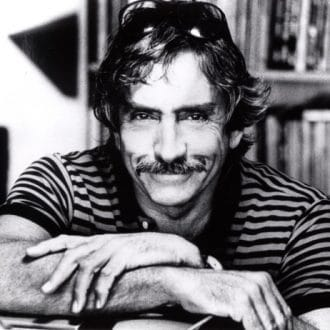 A young Edward Albee smiling with his arms crossed on a desk.