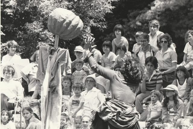 An outdoor production. The shot shows the audience reaction to the actress on stage.