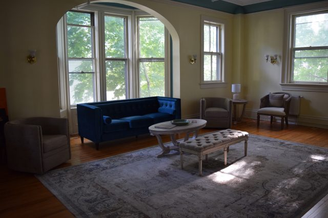 This photo showcases the high windows and natural light in the newly renovated parlor.