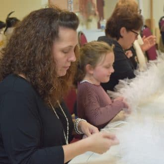 Parents and children are seated around a white table shaping tulle and wire into squirrel tails. Everyone is intensely concentrating on the task at hand, though some are smiling while they work.