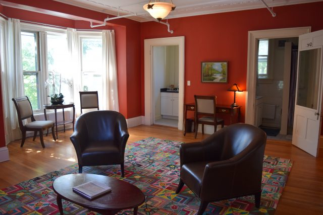 The image showcases the living space of the suite style Room 5 of Thaddeus Clapp House. Two chairs are framed in front with entrances to the kitchen and bathroom flanking the desk on the opposite wall.