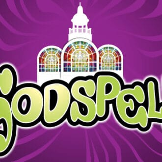 The opening image in the article is the Godspell logo. It is a purple background, with lighter purple rays radiating from the central image. At the center is the iconic Berkshire Theatre cupola with three arched stained glass windows. The title Godspell is just below and slightly overlapping this image. The text of Godspell is a groovy 70s inspired font in green.