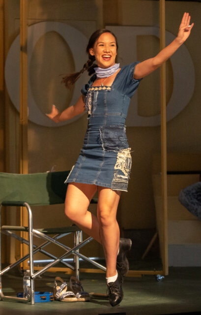 Kimberly Immanuel, one of the disciples, is tap dancing downstage in front of a green canvas and metal chair. Her arms are raised and one of her legs is bent as she is in the middle of a tap move.
