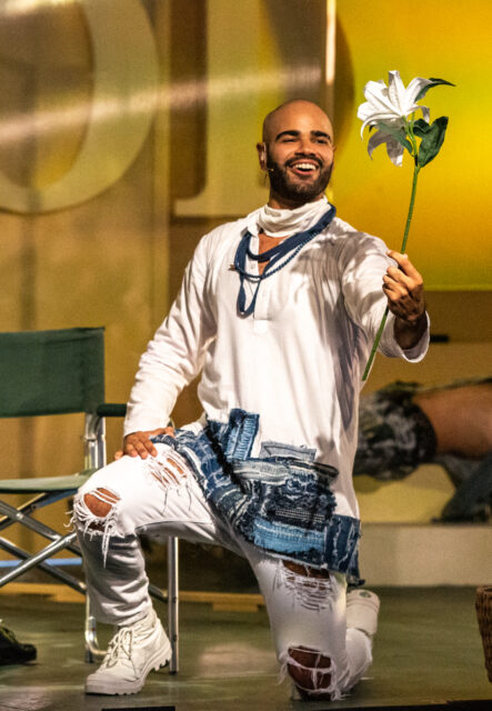 Jesus is kneeling downstage holding a large white flower by its long green stem. He is smiling at the flower lovingly. In the background, you can see another cast member reclining on their home base.