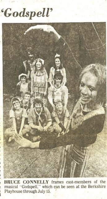 """This image is of a newspaper clipping with """"Godspell"""" at the top. It shows the actor playing Jesus framing the rest of the cast of Godspell in his arms in a forced perspective shot."""