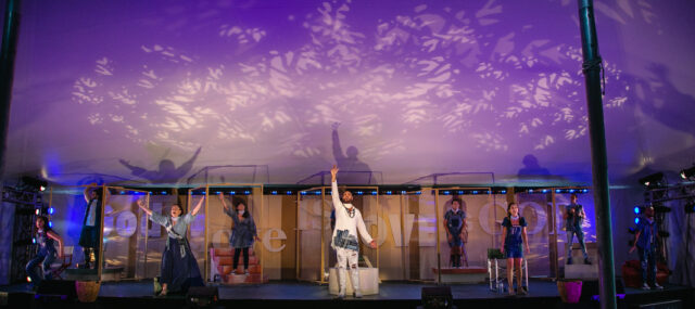 The ten cast members of Godspell are singing on stage, five in the back behind partitions and five in the front with Jesus front and center. Jesus is the only character in white, everyone else is in denim though each costume is unique. The stage is lit in purple with gobos creating a pattern on the ceiling of the tent.