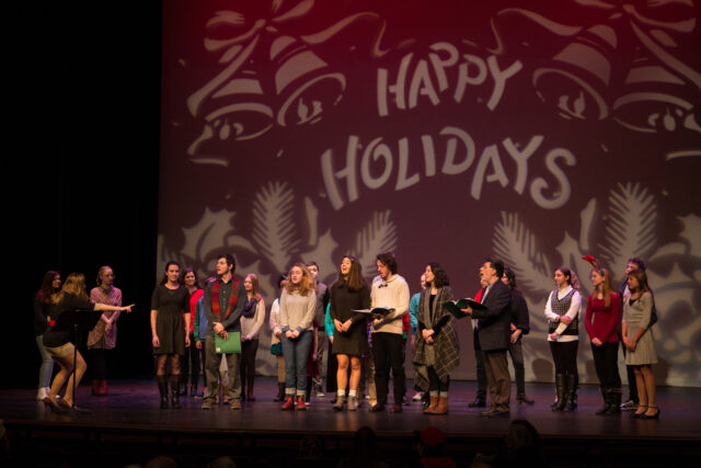 Rows of singers stand on stage singing. Behind them is a projection that reads Happy Holidays and has bows and holly around the words. There is a conductor down stage right directing the song.