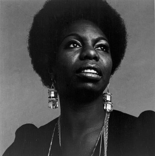 Photo of Nina Simone wearing a dark top with long dangly earrings, looking up and to the left.