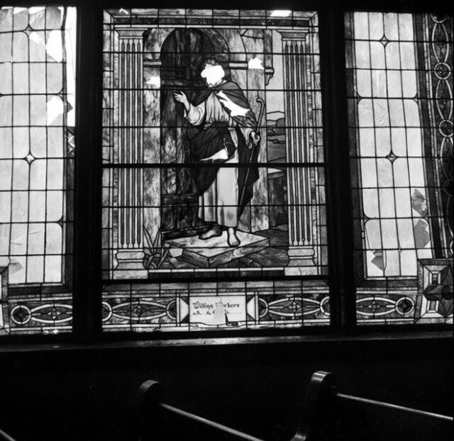 An image of the stained glass window after the bombing, there are noticeable chunks missing from the window, including the face of Jesus